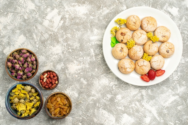 Вид сверху вкусное сладкое печенье с орехами и изюмом на белом фоне сахарный торт печенье конфеты