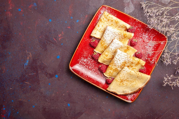 Top view of yummy sweet pancakes inside red plate with raspberries on black