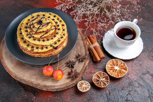 어두운 표면에 차 한잔과 함께 상위 뷰 맛있는 달콤한 팬케이크