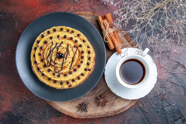 Vista dall'alto gustose frittelle dolci con una tazza di tè sulla superficie scura