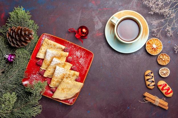 Vista dall'alto di deliziose frittelle dolci con una tazza di tè e lamponi su fondo nero