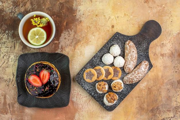 Vista dall'alto gustose frittelle dolci con una tazza di tè e dolci sulla scrivania leggera