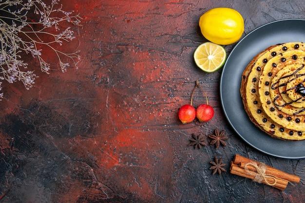Vista dall'alto gustose frittelle dolci con limone sulla superficie scura