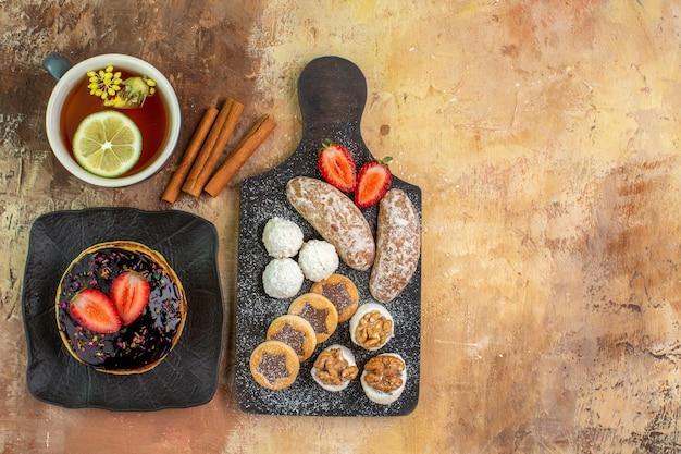 Вид сверху вкусные сладкие блины с чаем и сладостями на светлом столе