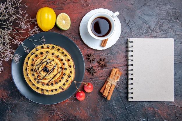 Vista dall'alto gustose frittelle dolci con tè sulla superficie scura
