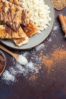 Вид сверху вкусная сладкая выпечка нарезанный творог на темном фоне печенье бисквит сахарное сладкое пирожное тесто