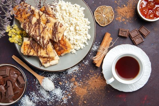 Вид сверху вкусная сладкая выпечка нарезанный творог чай на темном фоне печенье бисквит сахарное сладкое пирожное печенье