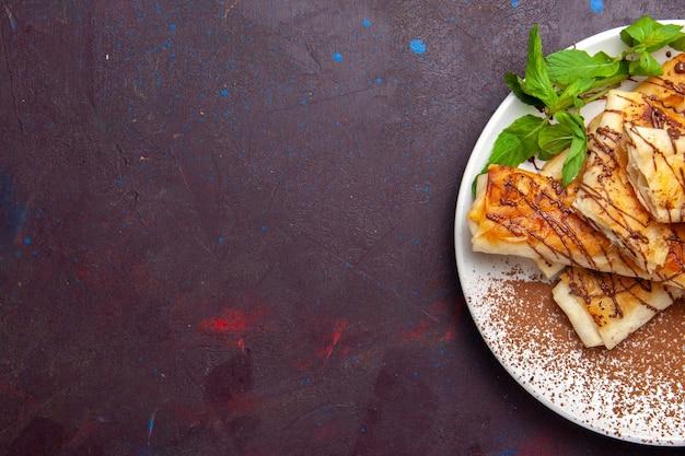 トップビューダークデスククッキービスケットシュガースイートケーキティーのプレートの内側にスライスされたおいしい甘いペストリー