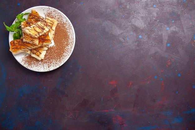 Вид сверху вкусной сладкой выпечки, нарезанной внутри тарелки на темном фоне, печенье, печенье, сахар, сладкий торт, чай