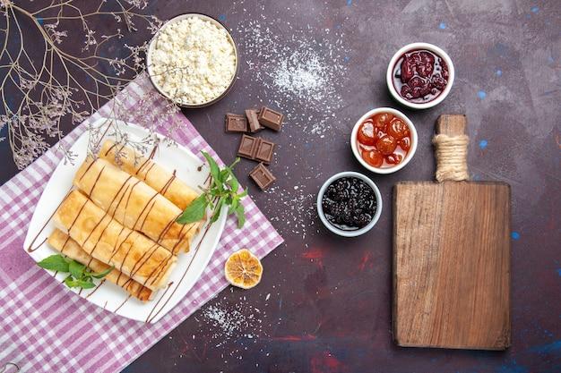 Вид сверху вкусная сладкая выпечка с творогом и джемом на темном фоне печенье бисквит сахар чай сладкий торт