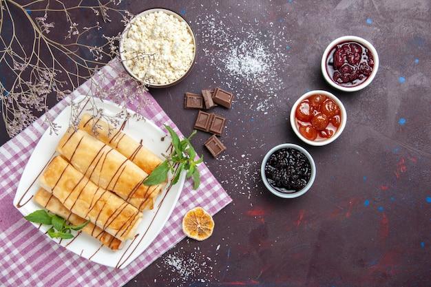 トップビューカッテージチーズと暗い背景のジャムとおいしい甘いペストリークッキービスケットシュガーティースウィートケーキ