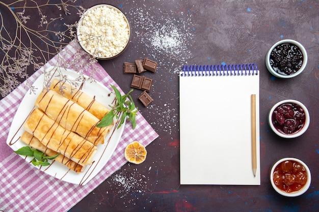 어두운 배경 쿠키 비스킷 설탕 차 달콤한 케이크에 코티지 치즈와 잼 상위 뷰 맛있는 달콤한 파이