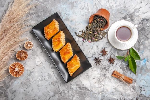 Vista dall'alto gustosi pasticcini dolci con una tazza di tè su torta di pasticceria bianca dolce