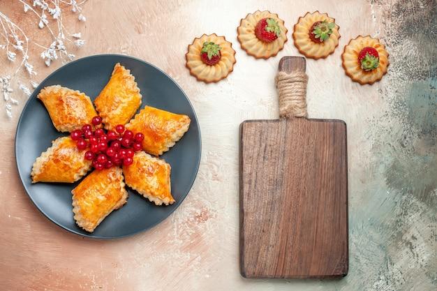 Вид сверху вкусной сладкой выпечки с красными ягодами на белом полу, пирог, торт, пирожное, сладкое