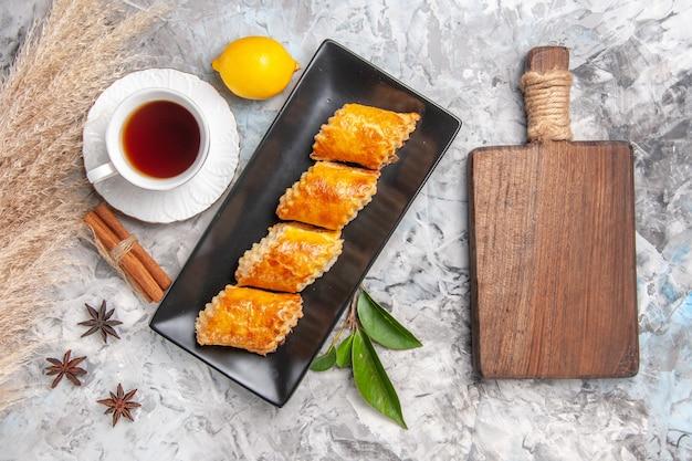 Vista dall'alto gustosi pasticcini dolci con tè su torta di pasticceria dolce bianca chiara