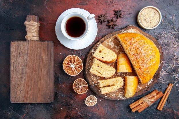 Vista dall'alto gustosa pasticceria dolce con una tazza di tè sulla superficie scura