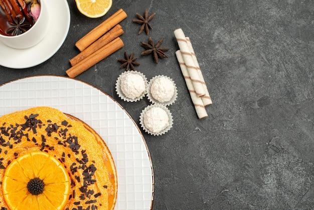 Vista dall'alto squisita torta dolce con una tazza di tè su superficie grigia dessert torta dolce torta biscotto tè
