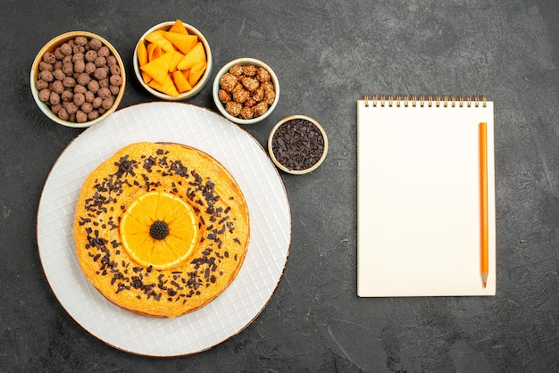 Top view yummy sweet pie with orange slices on the grey surface biscuit dessert sweet pie cake tea
