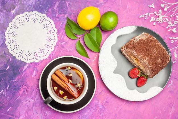 Vista dall'alto gustoso rotolo dolce con una tazza di tè su sfondo rosa