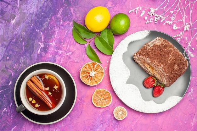 Vista dall'alto gustoso rotolo dolce con una tazza di tè sulla scrivania rosa