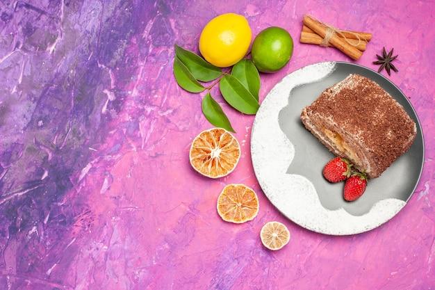 Вид сверху вкусный сладкий ролл с лимонами на розовом фоне
