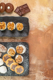 Vista dall'alto squisiti dolci con biscotti e caramelle sulla scrivania in legno