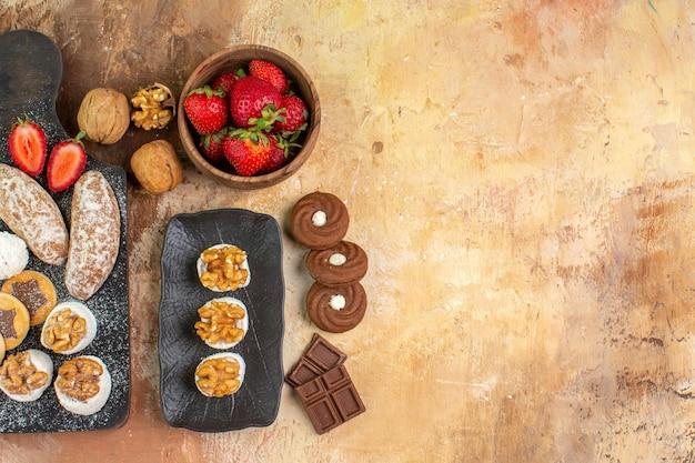 Vista dall'alto gustosi dolci con frutta caramelle e biscotti sulla scrivania in legno