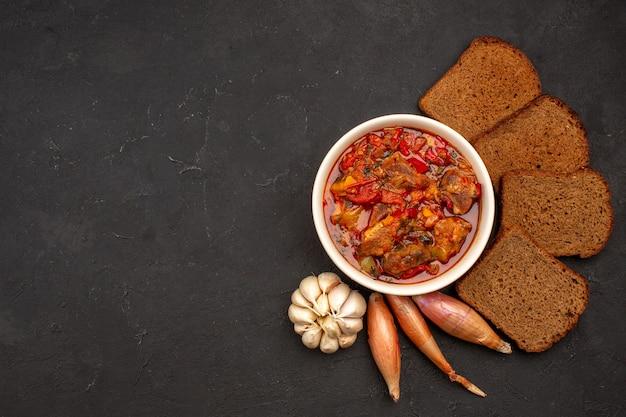 Vista dall'alto gustosa zuppa di verdure con pagnotte di pane scuro su oscurità
