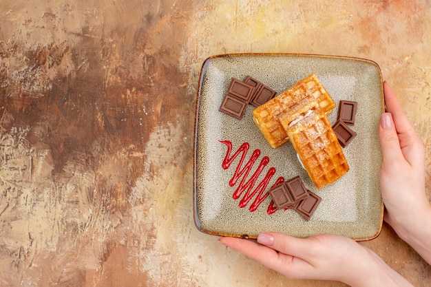 Top view yummy waffle cakes with chocolate bars on brown background
