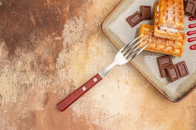 Vista dall'alto gustose torte waffle con barrette di cioccolato sullo sfondo marrone