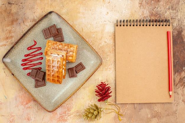 Вид сверху вкусные вафельные коржи с шоколадными батончиками на коричневом фоне