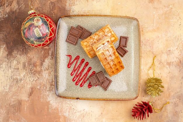 茶色の背景にチョコレートバーとトップビューおいしいワッフルケーキ