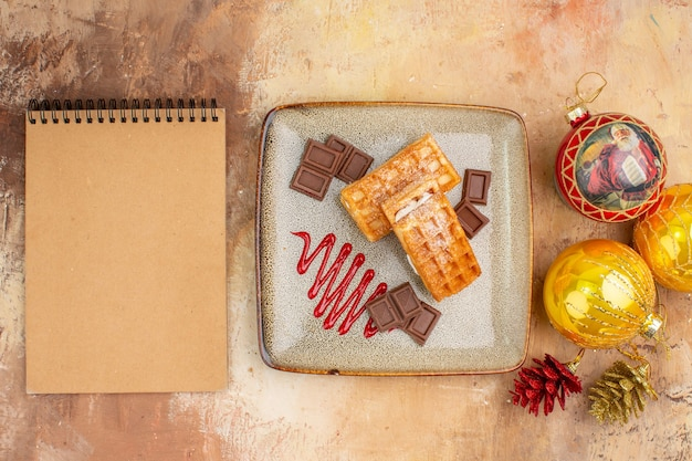 Top view yummy waffle cakes with chocolate and new year tree toys on light background