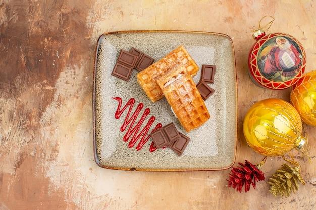 Vista dall'alto gustose torte waffle con cioccolato e giocattoli dell'albero di capodanno su sfondo chiaro