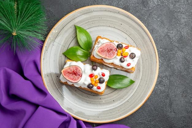 Вид сверху вкусные вафельные торты с фруктами на темном фоне
