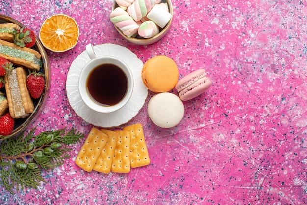 Top view of yummy waffle cookies with french macarons and cup of tea on pink surface