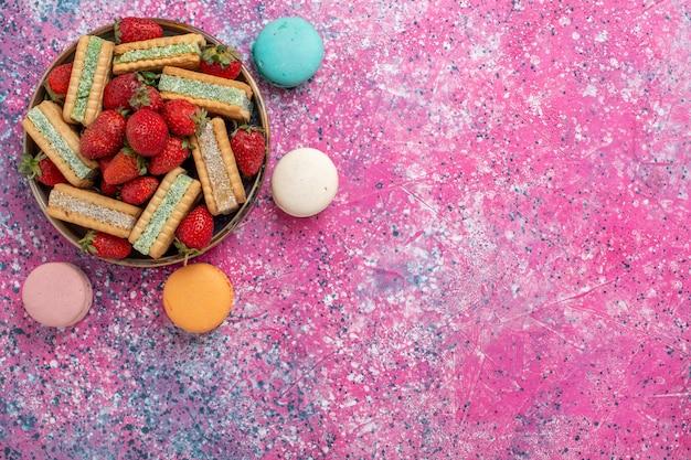 Vista dall'alto di gustosi biscotti waffle con fragole rosse fresche e macarons francesi sulla superficie rosa