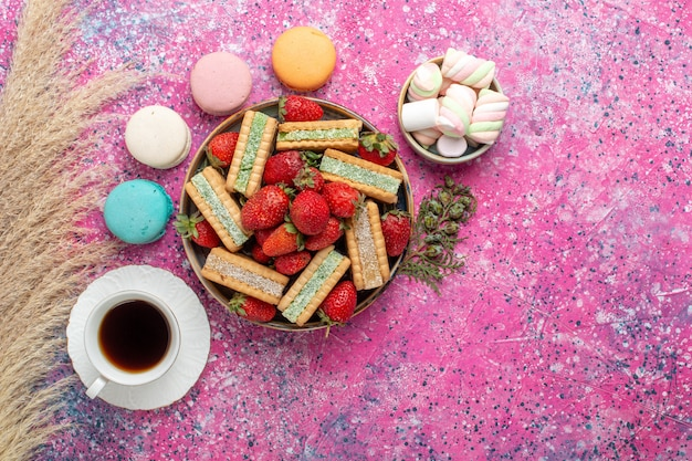 Top view of yummy waffle cookies with fresh red strawberries macarons and tea on pink surface