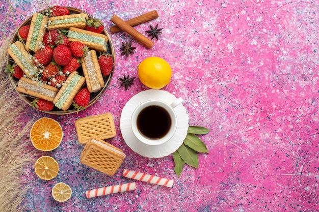 Vista dall'alto di gustosi biscotti waffle con fragole rosse fresche sulla superficie rosa