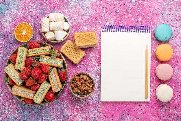 Vista dall'alto di deliziosi biscotti waffle con macarons e fragole rosse fresche sulla superficie rosa