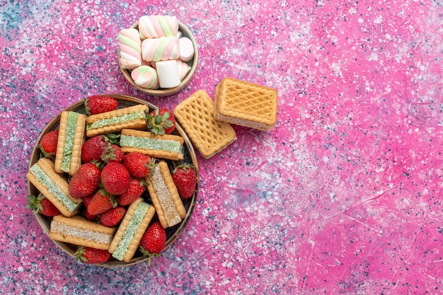 Top view of yummy waffle cookies with marshmallows and fresh red strawberries on pink surface