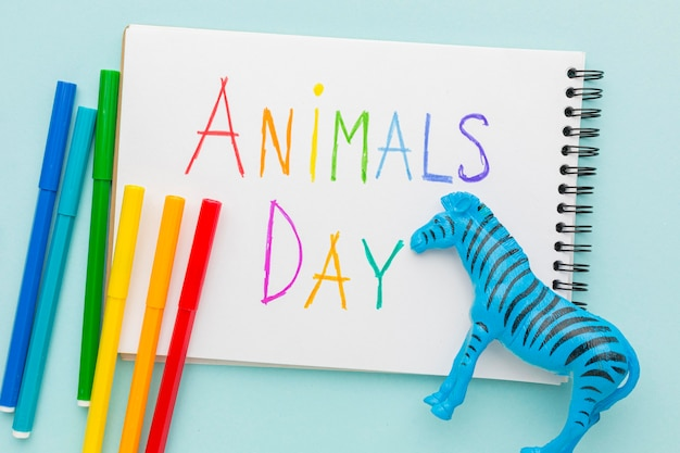 Top view of zebra figurine and colorful writing on notebook for animal day
