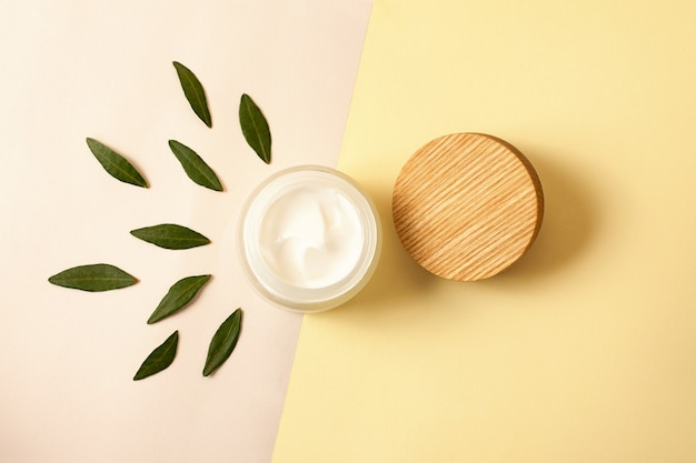Top view of the zero waste cosmetics container with green leafs aroundopen skin care packaging