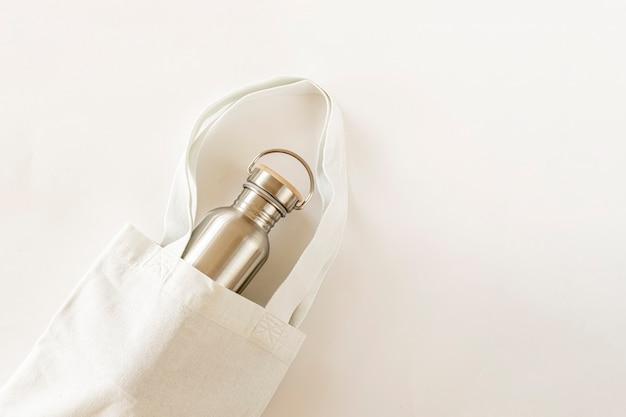 白い背景の上のビューゼロウェイストショッピングバッグと再利用可能なウォーターボトル