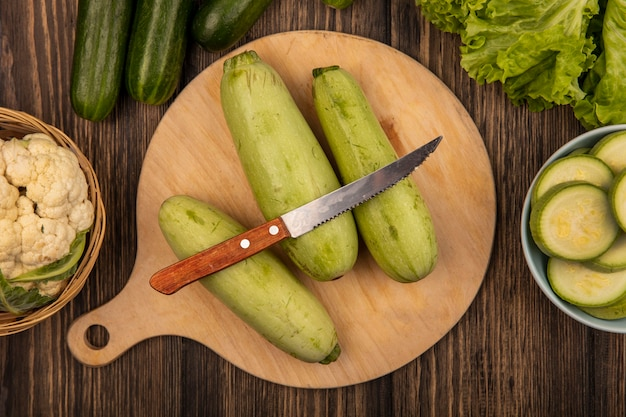 Top view of zucchinis isolated on a wooden kitchen board with knife with cauliflower on a bucket with cucumbers and lettuce isolated on a wooden surface