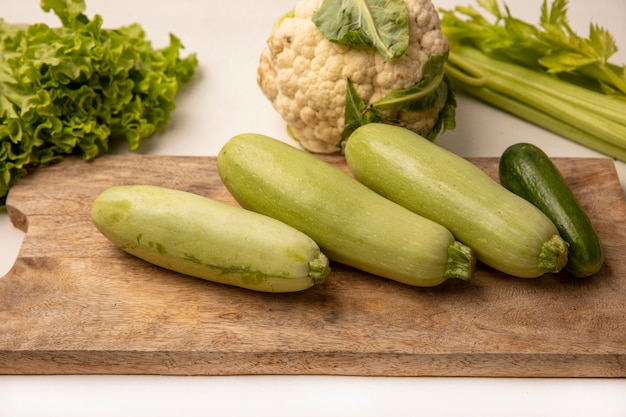 Top view of zucchinis on a wooden kitchen board with cucumbers lettuce celery and cauliflower isolated on a white surface
