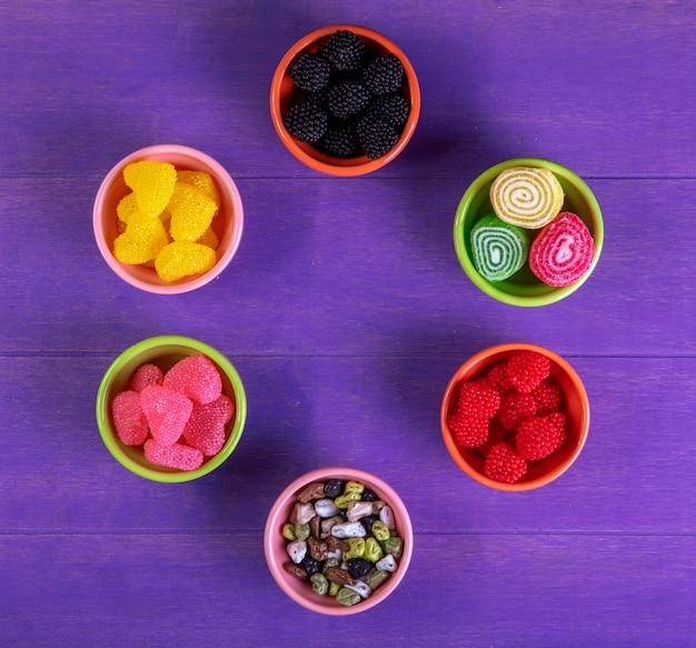 Vista dall'alto marmellata multicolore in diverse forme con caramelle al cioccolato a forma di pietra in piattini per marmellata su uno sfondo viola