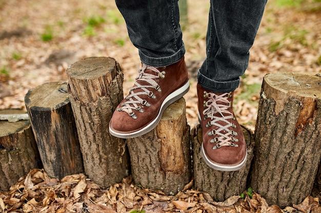 紅葉と木の背景にハイキングマウンテンブーツと立っているトップviewoman