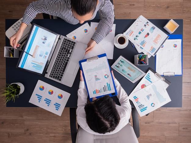 Vista dall'altovista dall'alto del manager e del dipendente che fanno il lavoro di squadra in ufficio, guardando i grafici sul display del laptop