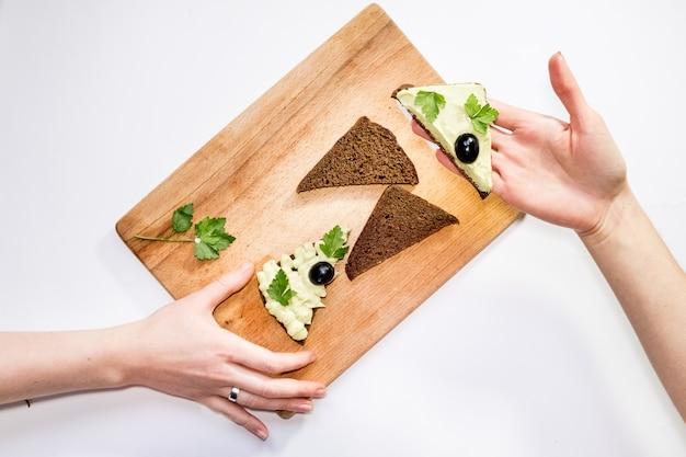 Top virew женщина держит свежий авокадо и делает бутерброды на столе с другими ингредиентами